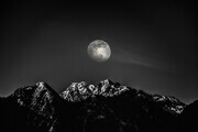 worm moon over snowcapped mountain